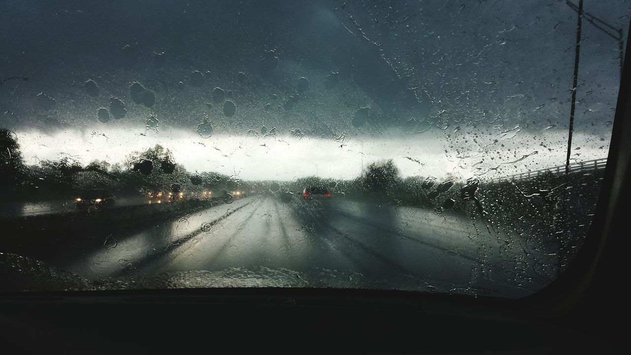 View of road seen through car windshield on rainy day
