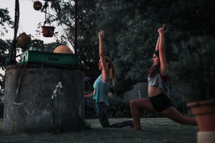 Side view of women with arms raised exercising in forest