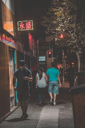 Rear view of woman walking on illuminated city