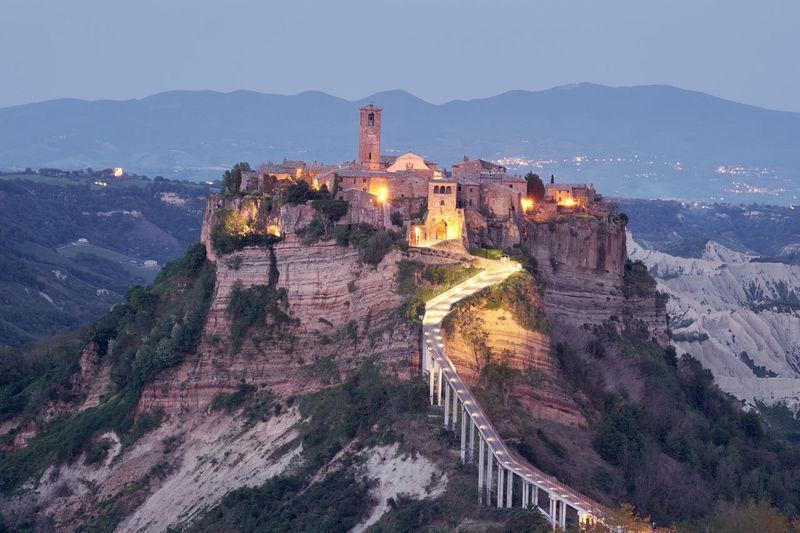 Illuminated fort on mountain against sky at dusk