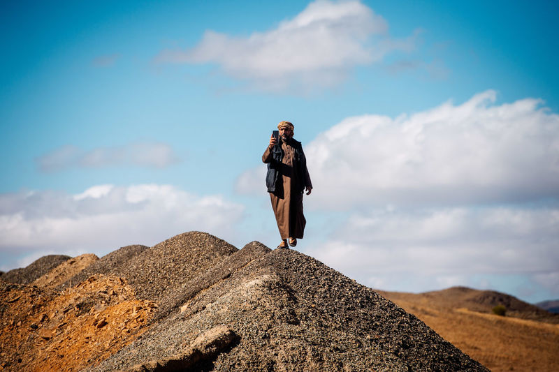 Low angle view of woman standing on rock against sky