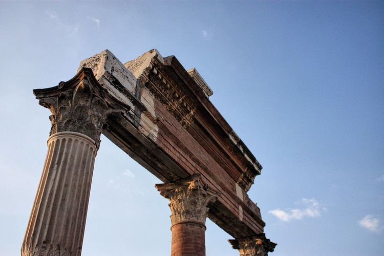 Low angle view of old ruined roman columns against sky