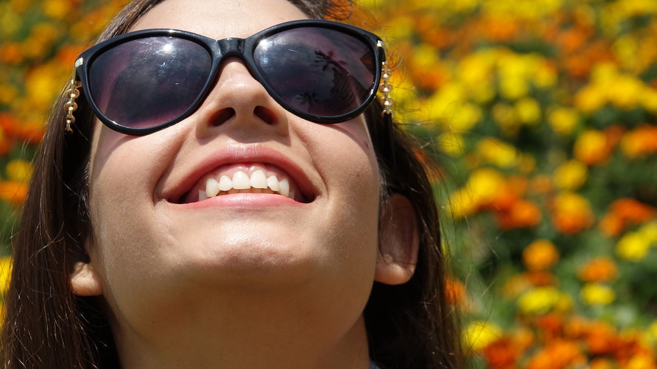 sunglasses, real people, one person, mouth open, leisure activity, childhood, lifestyles, outdoors, focus on foreground, happiness, human face, smiling, close-up, headshot, sticking out tongue, day