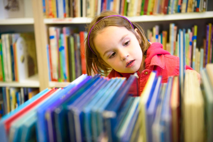 Girl selecting book while standing in library