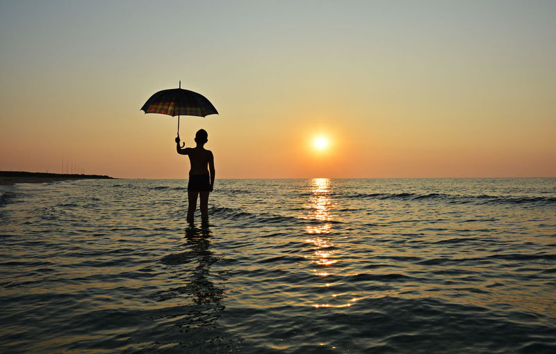 Conceptual image. Young boy with umbrella at the sunrise on the Corbu beach, Romania. Beach Beauty In Nature Boy Conceptual Holiday Horizon Over Water Idyllic Nature Ocean People Romania Scenics Sea Silhouette Sun Sunrise_Collection Sunset Sunset_collection Tourism Tranquil Scene Tranquility Umbrella Vacations Water Waterfront