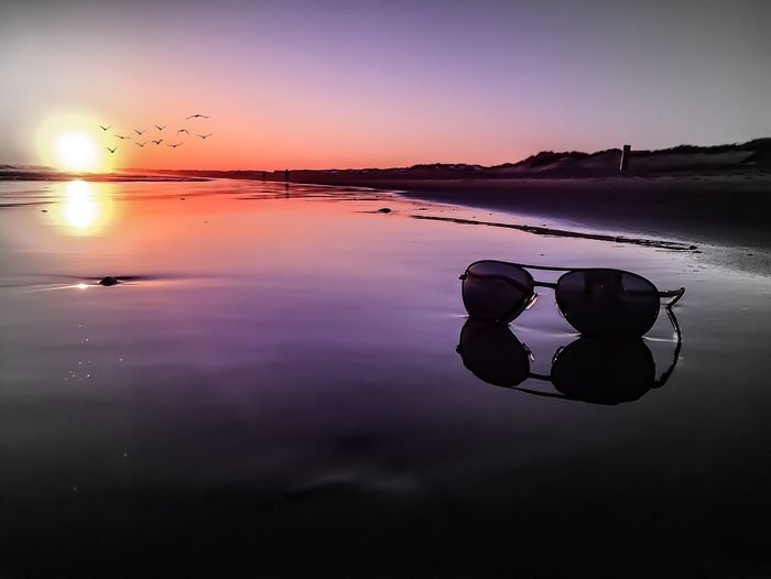View of sunglasses on beach at sunset
