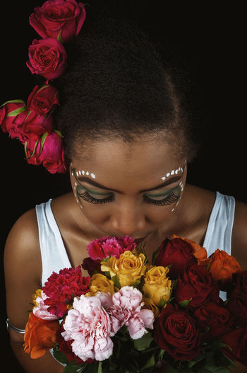 African Woman  Smiling Flowers Black Hair Natural Beauty Natural Hair Makeup Looking Down Flower Flowering Plant Plant One Person Front View Flower Arrangement Rosé Rose - Flower Flower Head Freshness Portrait Real People Headshot Bouquet Indoors  Fragility Vulnerability  Lifestyles Holding Women Black Background Hairstyle Bunch Of Flowers
