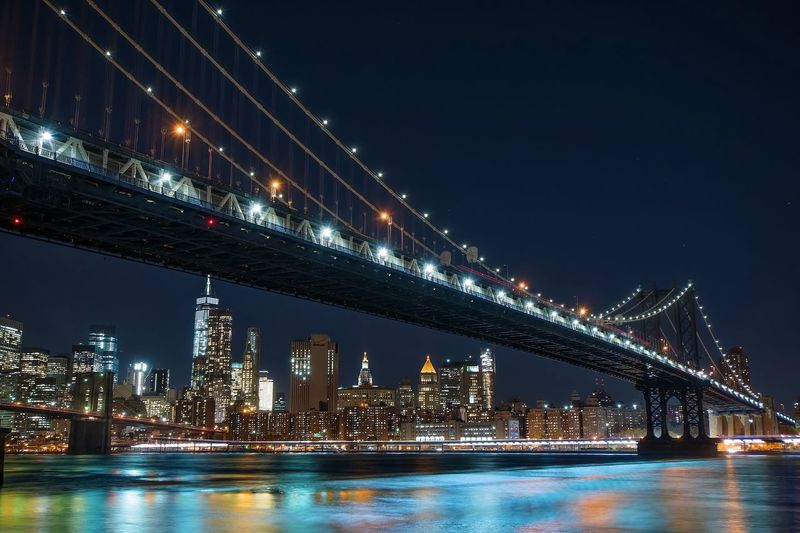 Manhattan bridge over east river against sky in illuminated city at night
