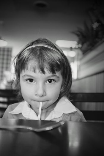 Portrait of girl with drinking straw in her mouth at restaurant