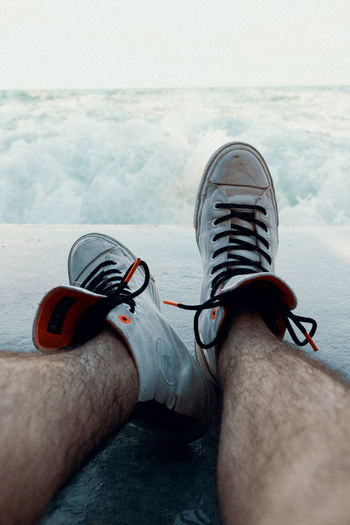 Low section of man wearing shoes on sea against sky