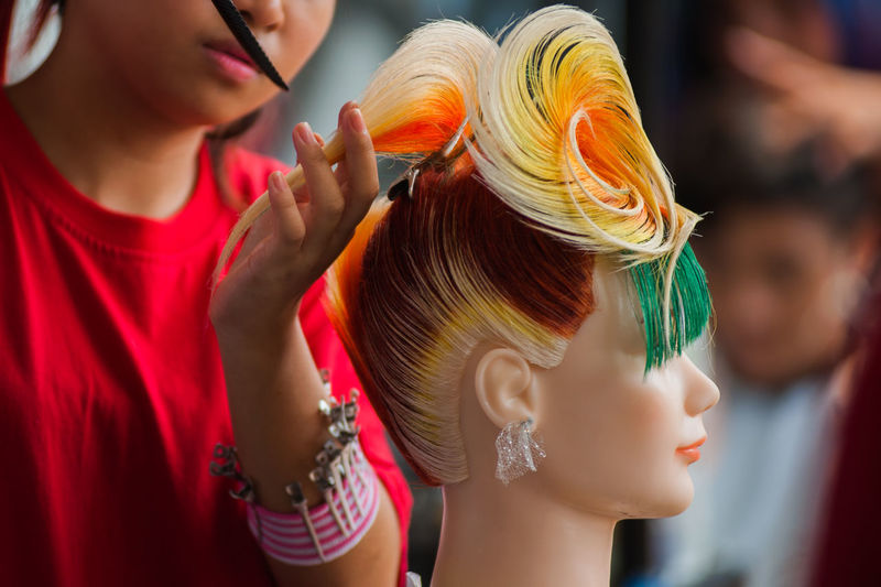 Young woman combing wig of mannequin