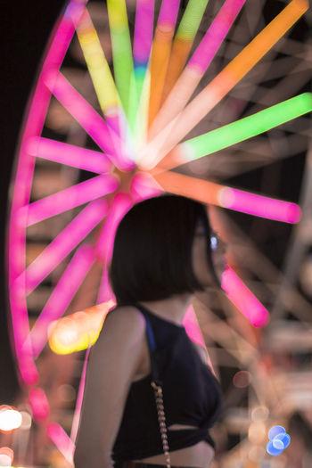 Woman Standing By Illuminated Ferris Wheel At Night