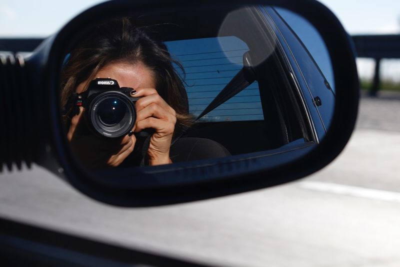 Reflection of woman on side-view mirror of car