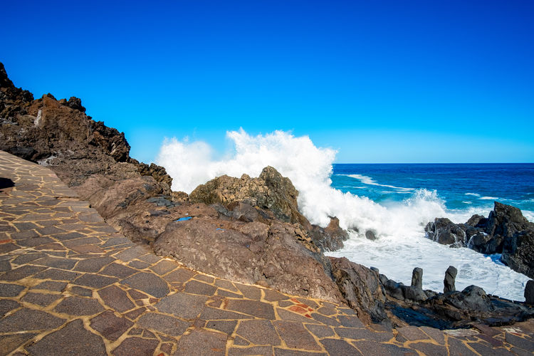 Scenic View Of Rocky Beach Against Blue Sky