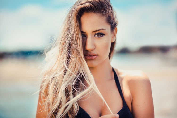 Close-Up Portrait Of Beautiful Young Woman Against Sea
