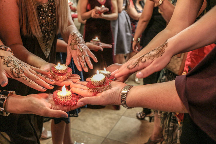 Female friends holding lit tea light candles while showing henna tattoos during ceremony