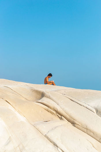 Shirtless man sitting on sand dune against clear blue sky