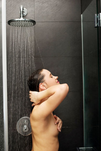 Shirtless woman taking shower in bathroom