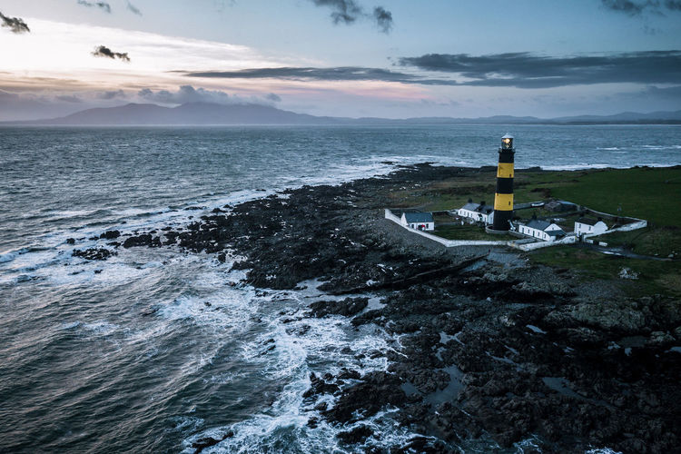 Aerial of the atlantic coast and black and blue lighthouse in Ireland near the ocean and sunset The Week On EyeEm Ireland Beach Beauty In Nature Cloud - Sky Day Guidance Horizon Over Water Lighthouse Nature No People Outdoors Scenics Sea Sky Tranquil Scene Tranquility Water Wave Shades Of Winter Fresh On Market 2018