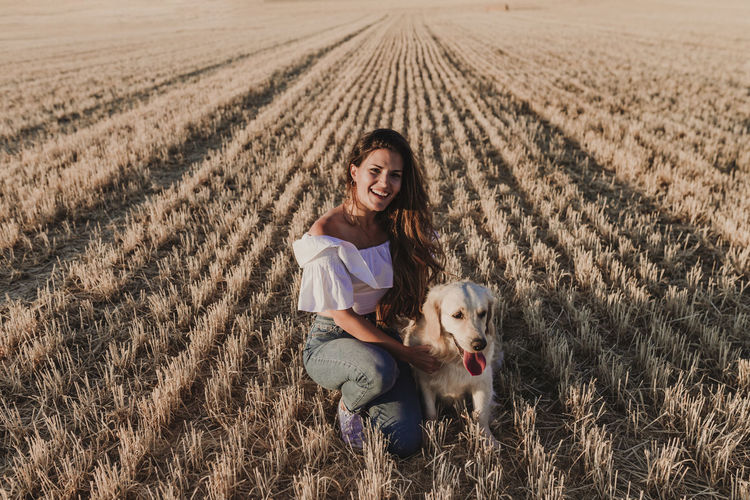 Portrait of smiling woman with dog on field