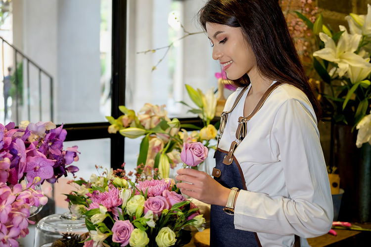 Smiling florist with flowers standing in store