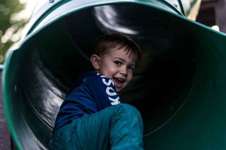 Low angle portrait of cheerful boy sitting in slide