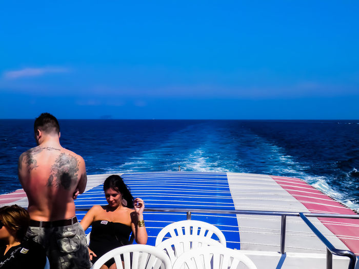 Rear view of couple sitting on sea against blue sky
