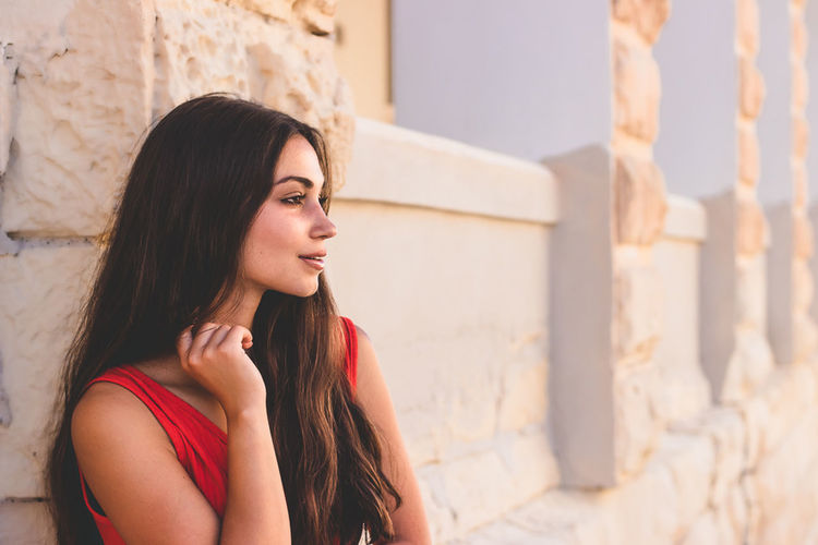 Portrait of beautiful young woman looking away against wall