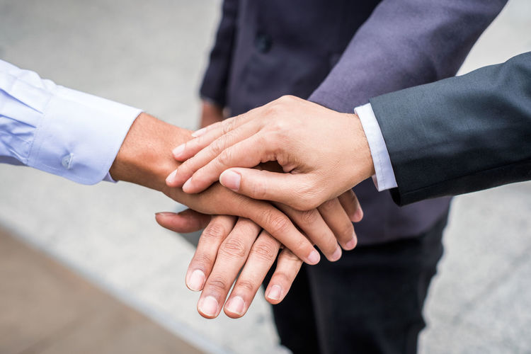 Close-up of business colleagues stacking hands