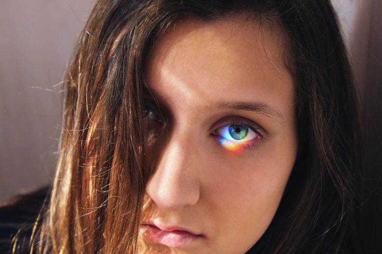 Close-up of spectrum falling on woman eye