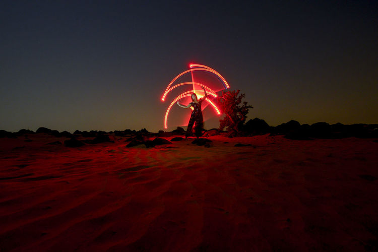 Illuminated ferris wheel on field against sky at night
