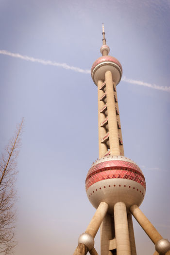 Low Angle View Of Oriental Pearl Tower Against Vapor Trail In Sky