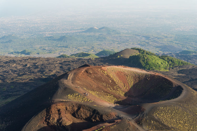 Group of tourists walking on the edge of the crater. fog at sunset over the volcano etna