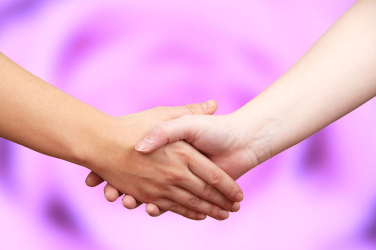 Cropped image of people shaking hands over purple background