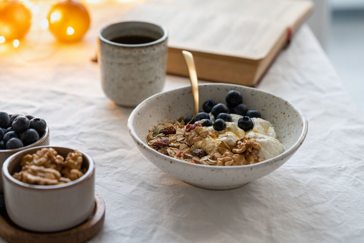 Reading book and eating healthy christmas holiday winter breakfast with granola muesli and yogurt