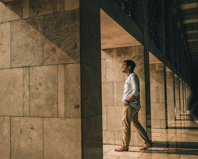 Side View Of Young Man Walking Amidst Architectural Columns In Corridor