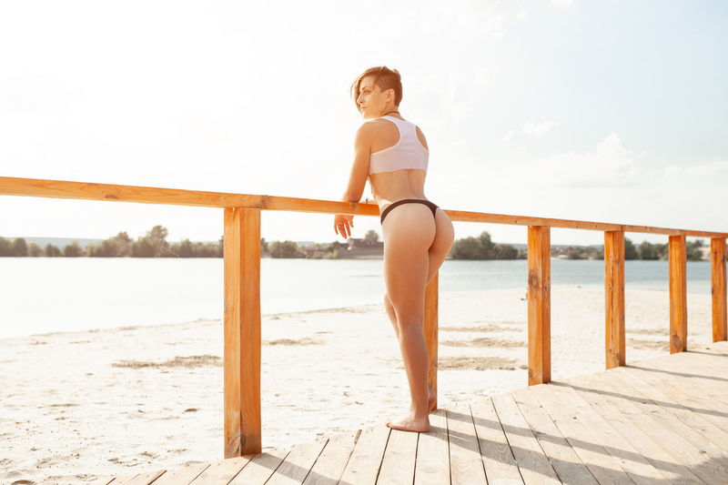 Sensuous woman standing by railing on pier at beach against sky