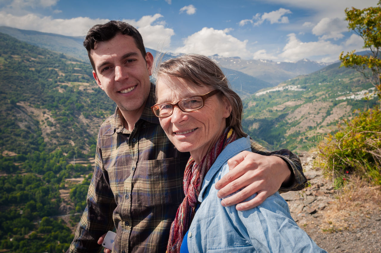 Portrait of young man with senior woman against mountains and sky