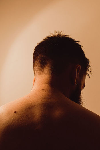 Rear view of shirtless man against wall