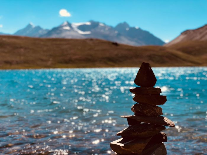 Stack of stones against lake and sky