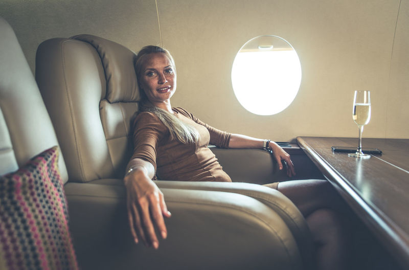 Portrait of businesswoman with wineglass in airplane