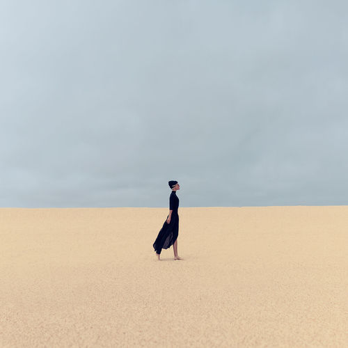 Stylish girl in black clothes walking in the desert
