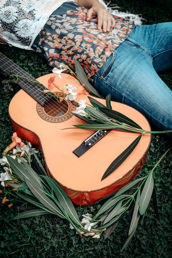 Cropped figure of hippie woman and a guitar lying on the grass in flowers. summer and freedom