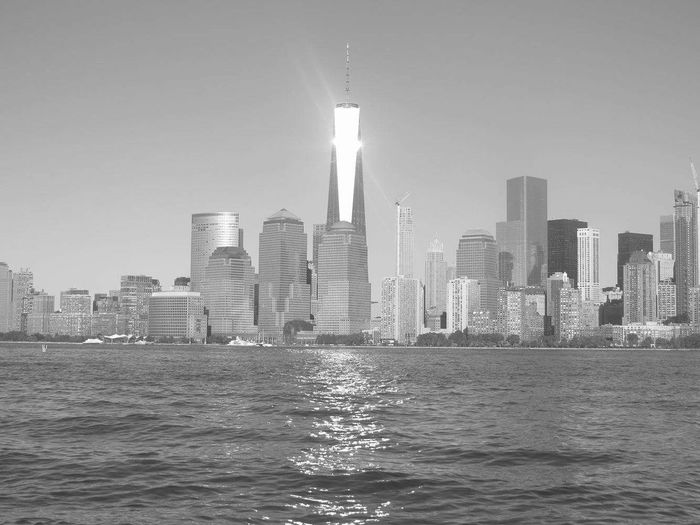 River against one world trade center amidst towers at manhattan