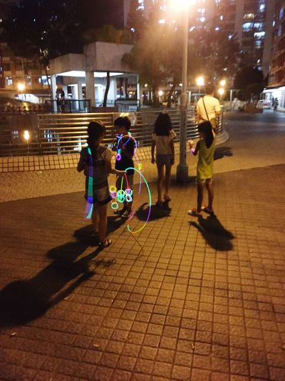 Illuminated Full Length City Street Building Exterior City Life Built Structure Architecture Night Togetherness Lifestyles Girls Person Outdoors Casual Clothing City Street Outline Footpath Student Children Outdoor Games