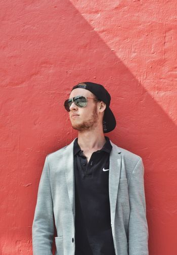 sunlight. Background Texture Red Sunlight Light Portraiture Moody Mood Sunglasses Wall - Building Feature Young Adult Young Men One Person Standing Outdoors Front View Day Lifestyles Leisure Activity Architecture Built Structure Portrait People Colour Your Horizn