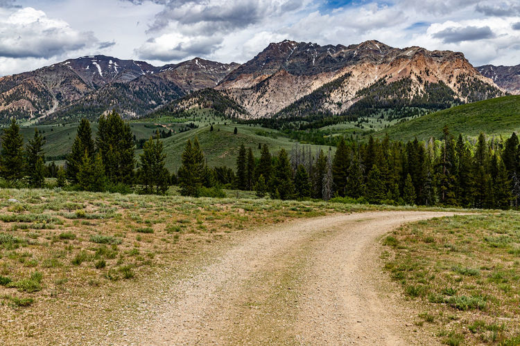 Dirt road by trees and mountains against sky