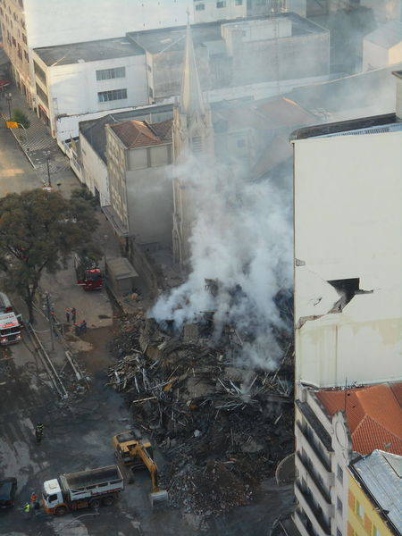 Day 2, Afternoon. Building Collapse: Inner City Calamity in downtown São Paulo at Largo do Paissandú; 3 am May 1, 2018. The abandoned former Federal Police steel and glass skyscraper, which had been invaded by street people, imploded in the early morning hours and the neighboring buildings, including the Lutheran Church on Avenida Rio Branco, were destroyed by fire as well. This photo taken in the afternoon of May 2, 2018 at Largo do Paissandú. It shows the round-the-clock efforts by firefighters and the debris removal crew. Afternoon Current Events Largo Do Paissandu May 1, 2018 May 2, 2018 Susan A. Case Sabir Unretouched Photography Building Collapse Building Fire Building Implosion Burning Building Controlled Chaos Dangerous Situation Debris Removal Downtown São Paulo Firefighters In Action Heat - Temperature High Angle View Implosion Responsiveness Smoke - Physical Structure Unexpected Event Urban Photography Urban Strife Work-in-progress
