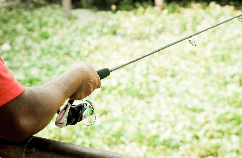 Close-up of man holding fishing rod