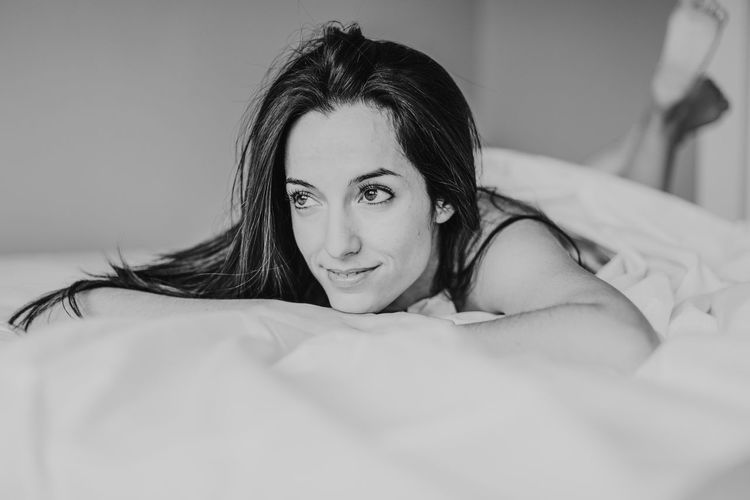 Thoughtful woman lying on bed